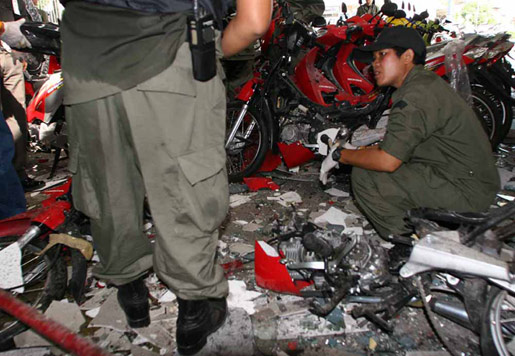 A Thai forensic police officer inspects a motorcycle showroom in Pattani province, southern Thailand, that was hit by arson on Aug. 2 .