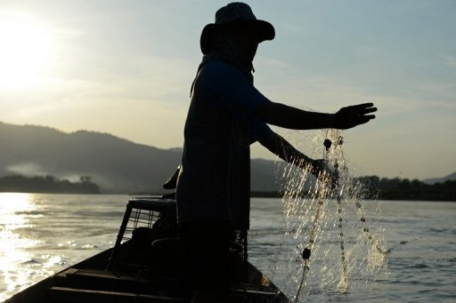 A fisherman stands on a boat as he lays his net in the Mekong river in Wiang Kaen, a district in the northern Thai province of Chiang Rai bordering Laos, on May 29, 2013. The waters of mighty Mekong have sustained generations of families but nowadays its fishermen often find their nets empty and fear hydropower mega-dams will destroy their livelihoods.