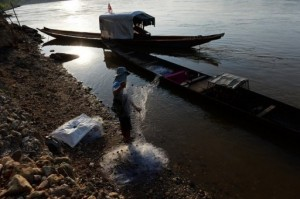 A fisherman stands on the bank of the Mekong river as he checks his net, in Wiang Kaen
