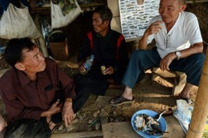 Fishermen and a buyer (R) eat fish as they sit in a hut on the bank of the Mekong river in Wiang Kaen