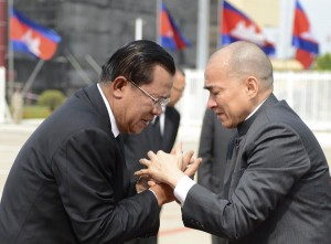 Cambodia's Prime Minister Hun Sen (L) greets Cambodia's King Norodom Sihamoni as the king arrives at Phnom Penh international airport before his departure for China