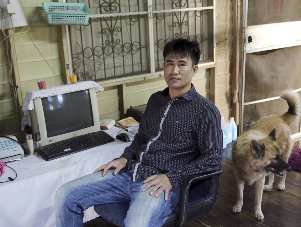 Thanawat Martnok poses for photographer with his dog at his house in Bangkok, Thailand.
