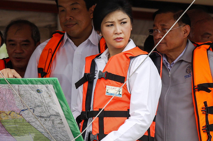 Thailand's Prime Minster Yingluck Shinawatra (2nd R) wears a life jacket as she consults with government officers during a visit to a flood area in Pathum Thani September 28, 2013. More than 600,000 Thais have been affected by flooding since July and more than a quarter of Thailand's provinces have been inundated, prompting officials to issue landslide warnings and begin evacuation measures on Monday. REUTERS/Athit Perawongmetha