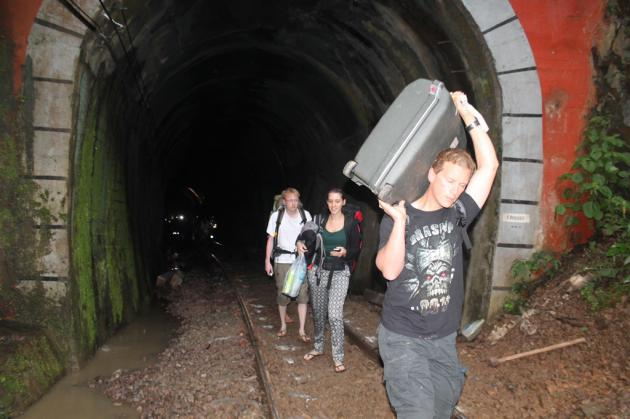 Passengers walk away from a derailed Bangkok-Chiang Mai overnight express train in Phrae's Den Chai district on July 17.