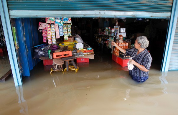 A resident walks outside a flooded shop at Srimahaphot district in Prachin Buri province, east of Bangkok, on September 24, 2013. More than 600,000 Thais have been affected by flooding since July.