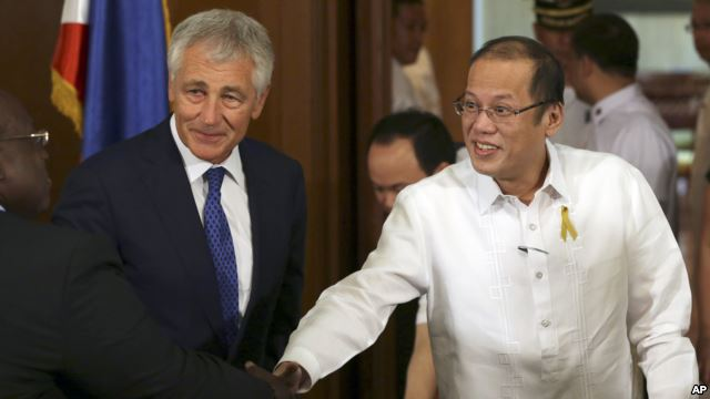 Philippine President Benigno Aquino III, right, shakes hands beside U.S. Defense Secretary Chuck Hagel, center, during his visit at the Malacanang Presidential Palace in Manila, Philippines
