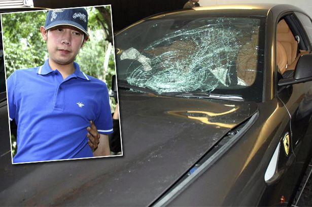 Vorayuth Yoovidhya, a grandson of late Red Bull founder Chaleo Yoovidhaya, is taken by a plain-clothes police officer for investigation, in Bangkok, Thailand. Thai authorities are seeking an arrest warrant for the heir to the Red Bull energy drink fortune after he failed to appear for his indictment in the hit-and-run death of a policeman, a prosecutor said Monday