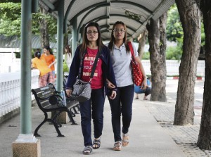 Jongkon Kongthin, 36, right, wife of Yuthapoom Martnok walks hand in hand with Yuthapoom's sister Pinyo Ruaylarp, 42, outside Remand Prison in Bangkok