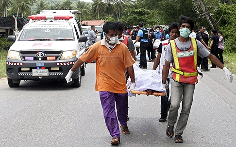 Rescue workers carry bodies after the fatal shooting of five police officers, in Tung Yang Daeng district of Pattani province, southern Thailand, on Wednesday