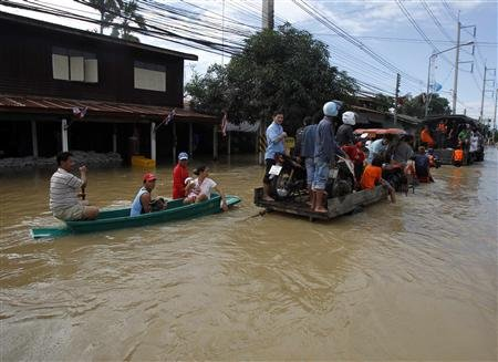 Residents sit on a loader and boat as it makes its way down a flooded street at Srimahaphot district in Prachin Buri province, east of Bangkok Photo /Chaiwat Subprasom