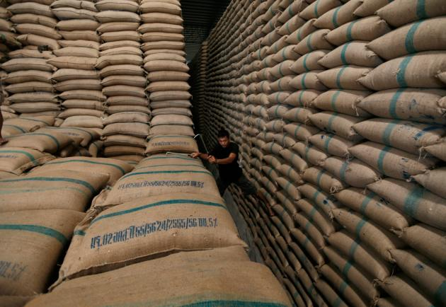 A worker amid sacks of rice stored under the government