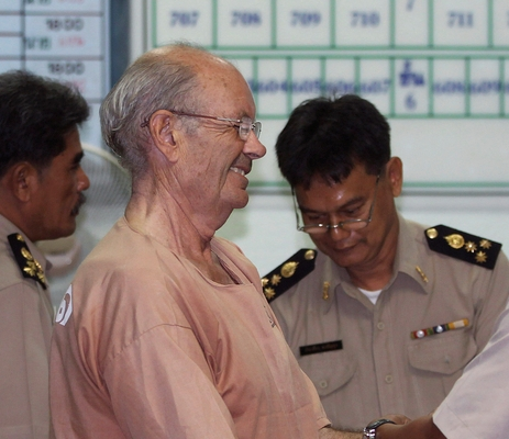 Suspected British paedophile David John Fletcher, left, is handcuffed before being led to hear extradition to Cambodia order at the criminal court in Bangkok, Thailand Wednesday, July 10, 2013. The Thai appeals court on Wednesday ruled to extradite Fletcher to Cambodia. Fletcher, 65, was arrested last year in Thailand after fleeing from Cambodia, where he was accused of sexual molestation and rapes of many girls under 15 years of age. (AP