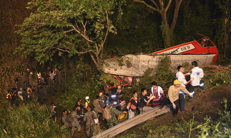 In this photo taken Wednesday, Oct. 23, 2013, Thai rescuers search for passengers of a bus that fell about 30 meters (98 feet) into the ravine on a curvy rural road in Lampang province, Thailand. The bus carrying worshippers home from a temple at the end of Buddhist Lent plunged into a ravine in northern Thailand, killing 22 passengers, police said Thursday.