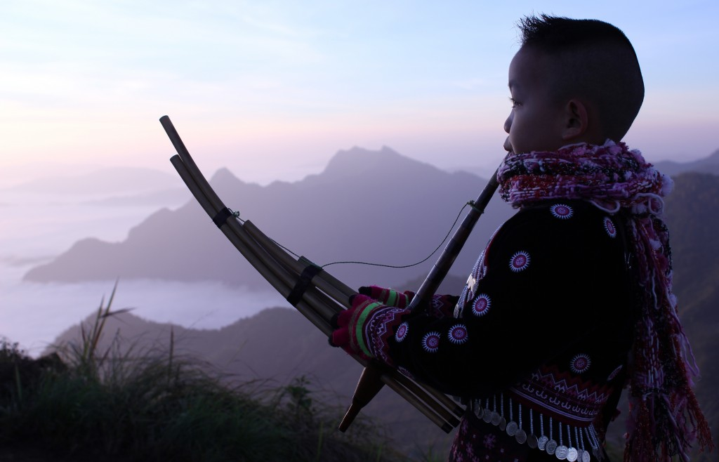 Phu Chee Fah Mountain, near Chiang Rai, Thailand, young Hmong boy playing the traditional bamboo reed instrument called the qeej for tourists