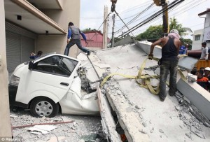 Workers use a crane to lift up a concrete block that fell on a car after buildings collapsed during an earthquake in Cebu city. At least 20 people in the Philippines have died in the earthquake Read more: http://www.dailymail.co.uk/news/article-2460461/Philippines-earthquake-death-toll-reaches-85-magnitude-7-2-quake.html#ixzz2hn2D2GBv Follow us: @MailOnline on Twitter | DailyMail on Facebook
