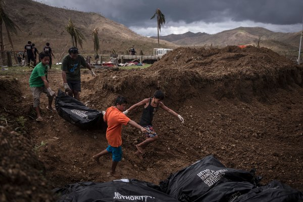 Volunteers lowered bodies into a mass grave on Thursday in Tacloban.
