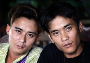 """Johnny, left, and his twin brother Luther Htoo pose for photos after their reunion at a restaurant in Sangkhlaburi district of Kanchanaburi province, western Thailand. When they were kids, Johnny and Luther Htoo were bulletproof and invulnerable to land mines - or so went the story that briefly made them famous as hundreds of guerrillas followed and even worshipped them in the southeastern jungles of Myanmar. Today, well over a decade later, their """"God's Army"""" is no more, and the twins' greatest accomplishment may be that both are still alive."""