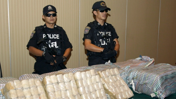 Drug Suppression Police guard packages containing about two million methamphetamine pills prior to a press conference in Bangkok, Thailand.