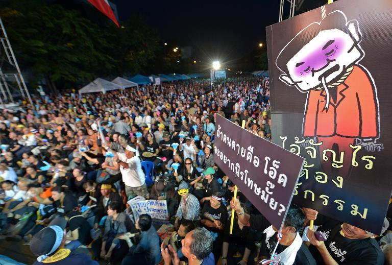 Thai opposition protesters hold protest placards as they rally against a planned amnesty at a railway station in Bangkok