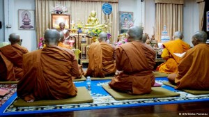 Bhikkhunis, or nuns, dressed in saffron colored robes, begin the day with a morning prayer.