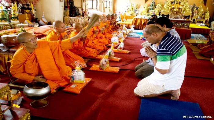 Dhammananda showers her family, including her two sons, with holy water in a religious ceremony