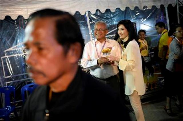 Protest leader Suthep Thaugsuban smiles with his wife Srisakul Promphan before addressing anti-government protesters as they take part in birthday celebrations for Thailand's revered King Bhumibol Adulyadej, at the occupied Government complex in Bangkok December 5, 2013. REUTERS/Dylan Martinez