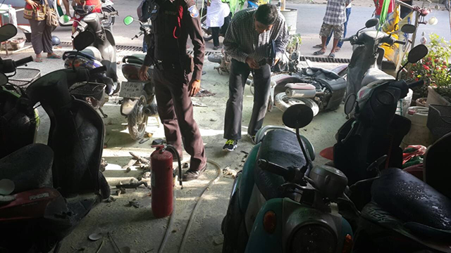 Police survey the damage at the motorcycle rental shop after the tourist's rampage