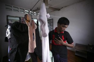 Bozor Mohammed from the Rakhine state in Myanmar puts his clothes, which were hung out to dry, inside his house after an interview with Reuters in Kuala Lumpur November 8, 2013. Picture taken November 8. REUTERS/Samsul Said