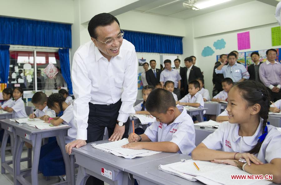 Chinese Premier Li Keqiang talks with third-grade pupils who are learning Chinese characters at a Chinese language-teaching school in Chiang Mai