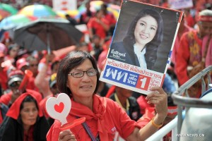 A red-shirt supporter holds a poster of Thai Prime Minister Yingluck