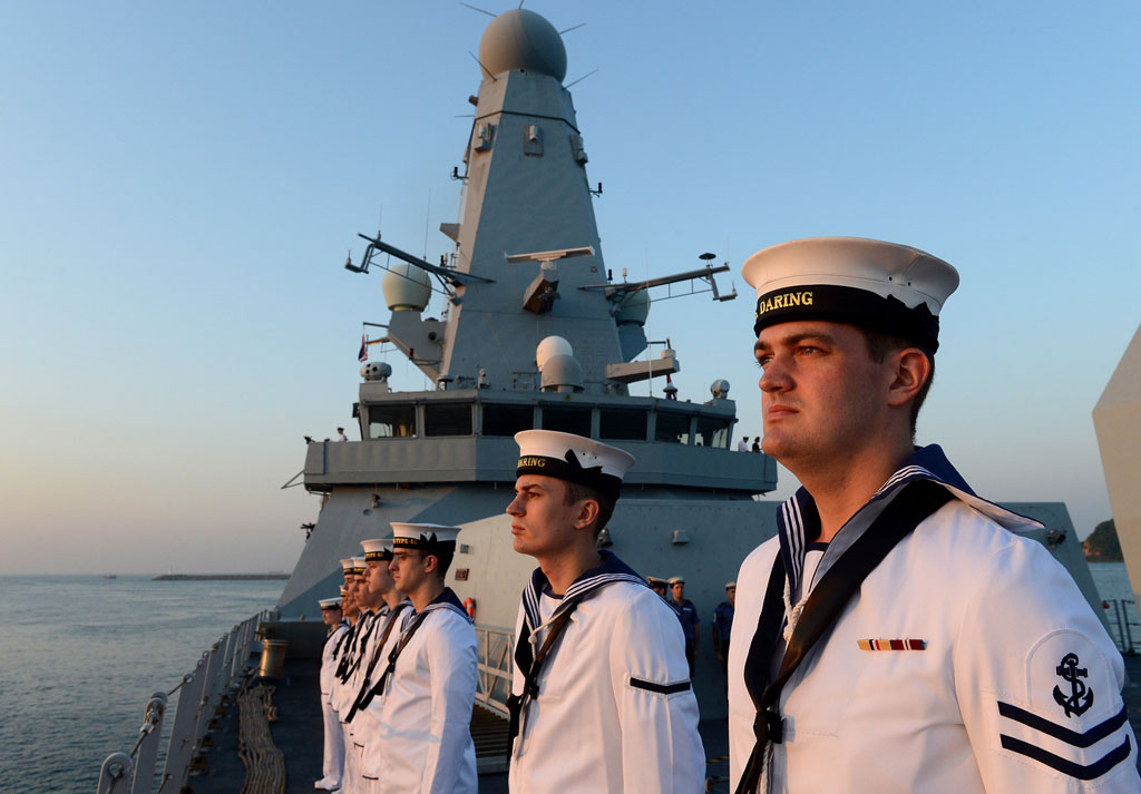 HMS Daring's Ship's Company line the upper deck at sunrise as the Type 45 comes alongside Sattahip, Thailand.