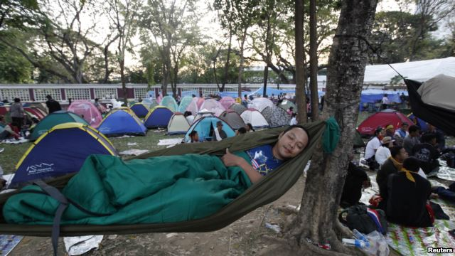 A Thai man sleeps in a park with fellow protesters in central Bangkok, Jan. 14, 2014.