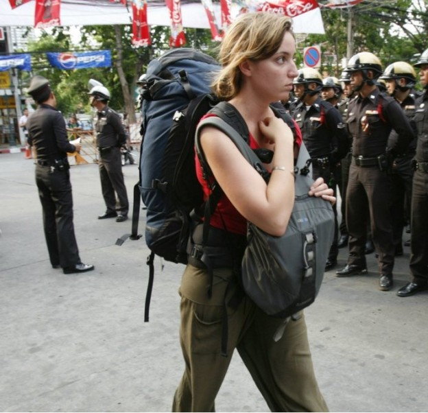 foreign tourists walk next to anti-government protesters at Government House in Bangkok