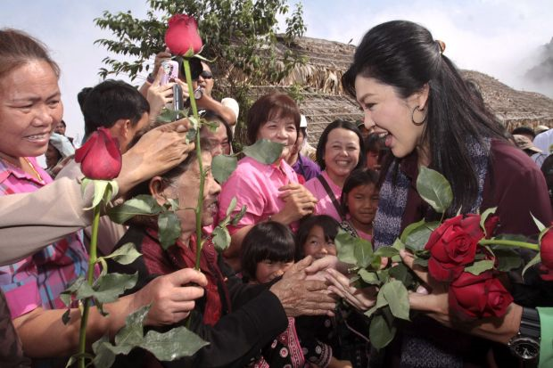 Thai caretaker Prime Minister Yingluck Shinawatra (R) receiving roses from supporters during her visit to a hill tribe village in Chiang Mai province, northern Thailand
