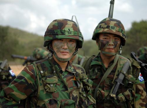 A female soldier (L) from the Republic of Korea poses with her comrade in arms during a landing drill of the Cobra Gold multinational military exercise in Sattahipp of Changwat Chon Bury, Thailand,
