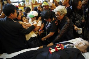 An anti-government protester pours water over the hand of killed protest leader Suthin Tharatin during his funeral ceremony in Bangkok