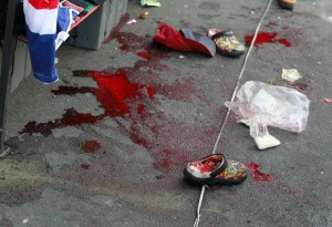 Puddles of blood and small pairs of shoes are seen at the site of an explosion at a main protest site in Bangkok, Thailand