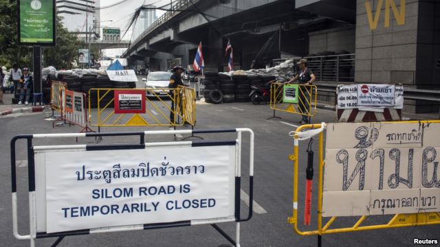 A sign indicating the closure of a main touristic road can be seen next to barricades of anti-government protesters near a main stage of the protest in Bangkok,
