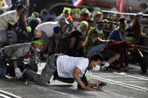 An anti-government protester crawls with his pistol during a gunfight between supporters and opponents of Thailand's government near Laksi district office in Bangkok February 1, 2014. REUTERS/ Nir Elias