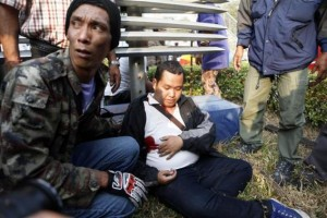 A man who was on the pro-government side is helped by pro-government protesters after being injured from gunfire during clashes in Bangkok February 1, 2014. REUTERS/ Nir Elias