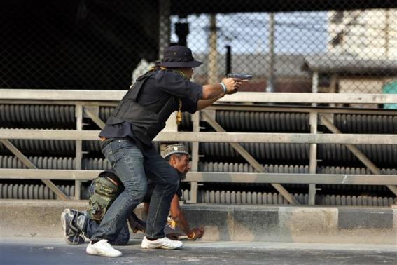 An anti-government protester shoots with his pistol during a gunfight between supporters and opponents of Thailand's government near Laksi district office in Bangkok February 1, 2014. REUTERS/ Nir Elias