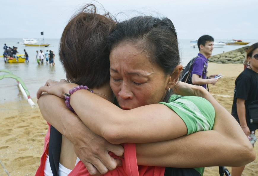 Members of a Japanese search party hug Monday after they received the news that survivors were found.