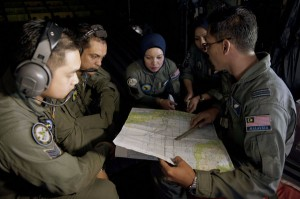 A captain of the Royal Malaysian Air Force, Izam Fareq Hassan, right, talked with his team members during a search and rescue operation over the Strait of Malacca