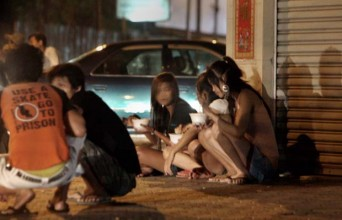 Cambodian homeless girls sit on the side walk along a street in Phnom Penh