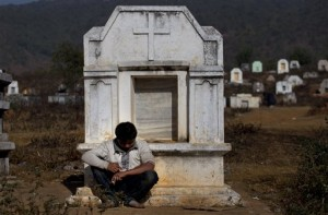 an addict leans on a white tombstone as he shoots up heroin at a cemetery in Nampatka village, northeastern Shan State