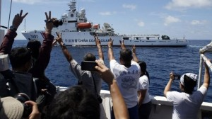 Philippine crew members flashed peace signs at the Chinese vessel