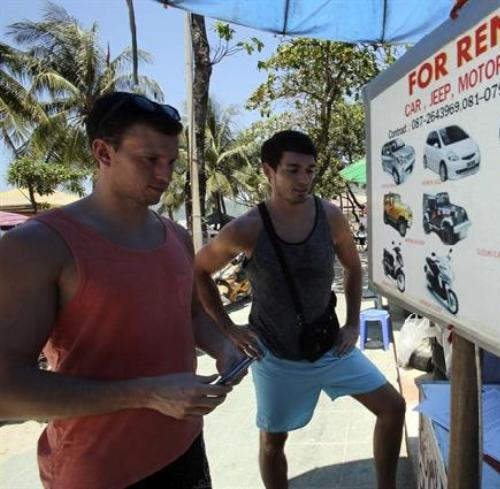 German tourist Falko Tillwich, left, holds his passport near his German friend, who didn't want to give his name as they try to contact a car rental on Pathong Beach in Phuket province, southern Thailand.