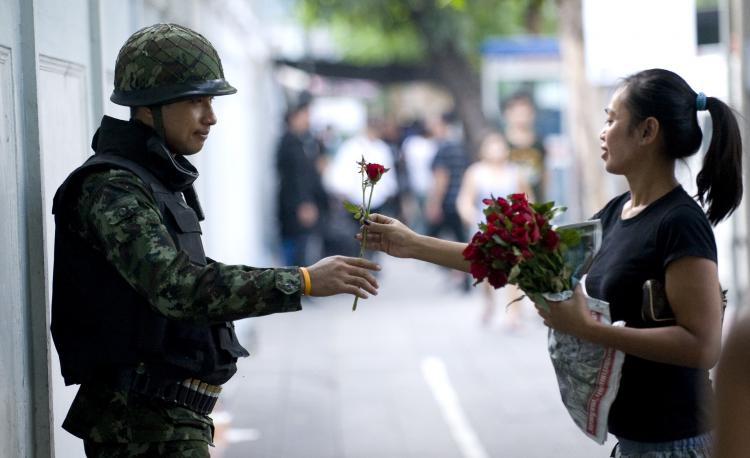 A Bangkok resident hands a soldier a rose in appreciation as he stands guard on Convent Road in Bangkok