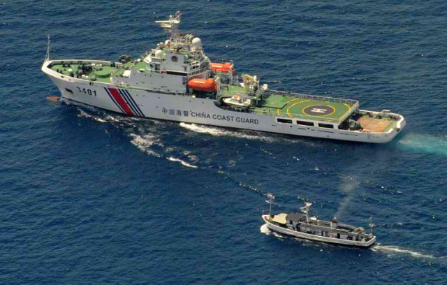 A China Coast Guard ship (top) and a Philippine supply boat engage in a stand off