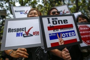 """People hold placards during a rally demanding their votes to be respected, while protesting against the court""""s ruling in central of Bangkok"""